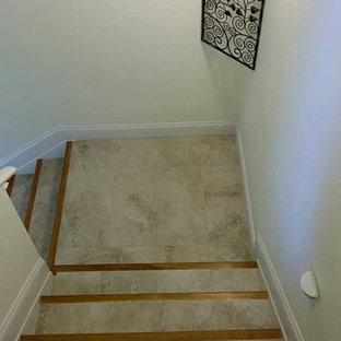 他の地域の中サイズのタイルのおしゃれな折り返し階段 (タイルの蹴込み板) の写真