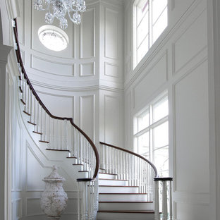 Staircase - large traditional wooden curved staircase idea in Miami with painted risers