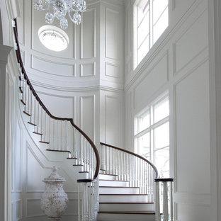 Imagen de escalera curva, clásica, grande, con escalones de madera y contrahuellas de madera pintada