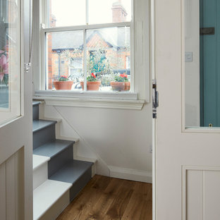 Example of a small danish painted l-shaped wood railing staircase design in Dublin with painted risers