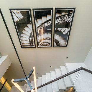 Foto de escalera suspendida y papel pintado, actual, grande, con escalones de mármol, contrahuellas de mármol, barandilla de metal y papel pintado