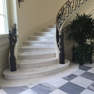 Ejemplo de escalera curva, clásica, grande, con escalones de mármol, contrahuellas de mármol y barandilla de metal