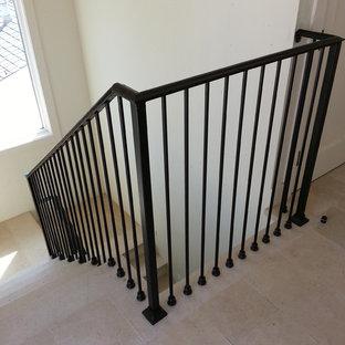 Ejemplo de escalera en U, minimalista, de tamaño medio, con escalones con baldosas, contrahuellas con baldosas y/o azulejos y barandilla de metal
