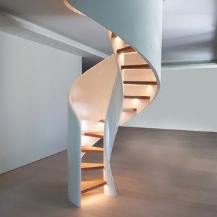 Foto di una scala a chiocciola contemporanea con pedata in legno e nessuna alzata