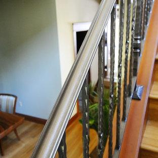 """Foto di una scala a """"U"""" tropicale di medie dimensioni con pedata in legno, alzata in legno e parapetto in metallo"""