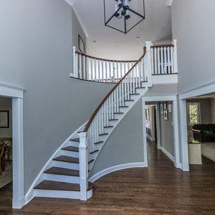 Imagen de escalera curva, de estilo americano, grande, con escalones de madera, contrahuellas de madera pintada y barandilla de madera