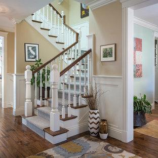 Ejemplo de escalera en U, tradicional, con escalones de madera y contrahuellas de madera pintada