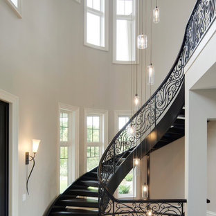 Example of a huge classic wooden curved open and metal railing staircase design in Minneapolis
