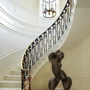 Immagine di un'ampia scala curva tradizionale con pedata in marmo e alzata in marmo