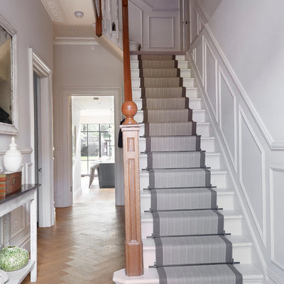 Elegant painted l-shaped staircase photo in London with painted risers