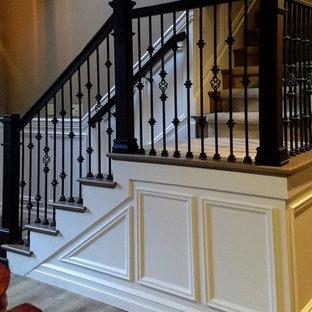 Diseño de escalera en L y boiserie, clásica, de tamaño medio, con escalones enmoquetados, contrahuellas de madera, barandilla de metal y boiserie