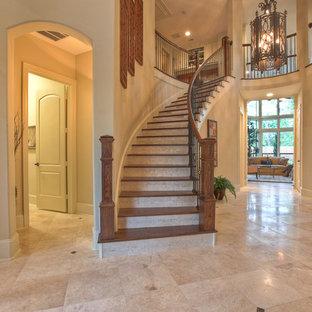 Пример оригинального дизайна: лестница в классическом стиле с деревянными ступенями, подступенками из травертина и перилами из смешанных материалов