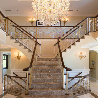 Large elegant marble l-shaped metal railing staircase photo in Vancouver with marble risers