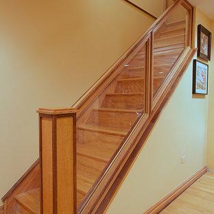 Diseño de escalera recta, tradicional, de tamaño medio, con escalones de madera, contrahuellas de madera y barandilla de vidrio