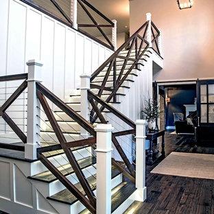 Ejemplo de escalera en L, de estilo de casa de campo, extra grande, con escalones de madera, barandilla de varios materiales y contrahuellas de madera pintada