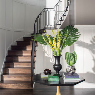 Example of a large transitional wooden curved metal railing staircase design in Los Angeles with wooden risers