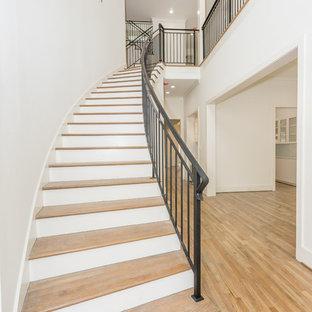 Diseño de escalera curva, tradicional renovada, de tamaño medio, con escalones de madera, contrahuellas de madera pintada y barandilla de metal