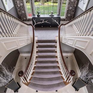 Foto de escalera en U, clásica renovada, grande, con escalones enmoquetados y contrahuellas de madera