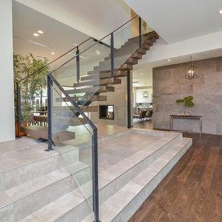 Foto de escalera suspendida, tradicional renovada, extra grande, sin contrahuella, con escalones de madera y barandilla de vidrio