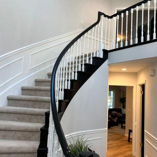 Exempel på en mellanstor klassisk svängd trappa, med heltäckningsmatta, sättsteg med heltäckningsmatta och räcke i trä