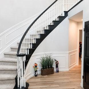 Modelo de escalera curva y boiserie, tradicional renovada, de tamaño medio, con escalones enmoquetados, contrahuellas enmoquetadas, barandilla de madera y boiserie