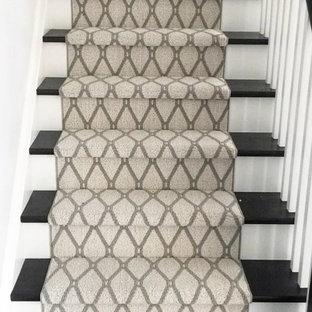 Imagen de escalera curva, tradicional renovada, de tamaño medio, con escalones de madera, contrahuellas de madera pintada y barandilla de madera