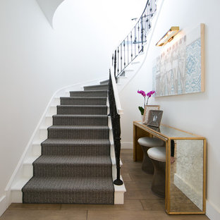 Transitional painted curved staircase photo in Orange County with painted risers