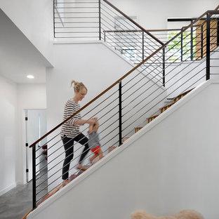Diseño de escalera en U, contemporánea, con escalones de madera y barandilla de cable