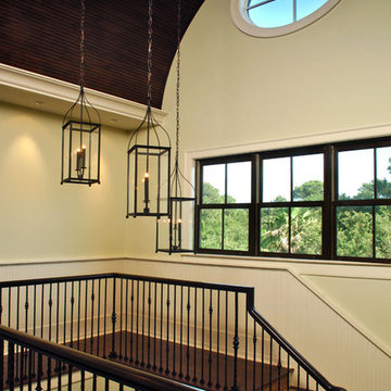 Trio of chandeliers at different heights adds interest to stairway