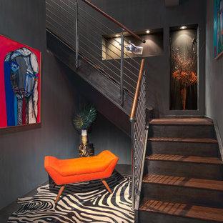 Exemple d'un grand escalier tendance en L avec des marches en bois, des contremarches en bois et un garde-corps en métal.