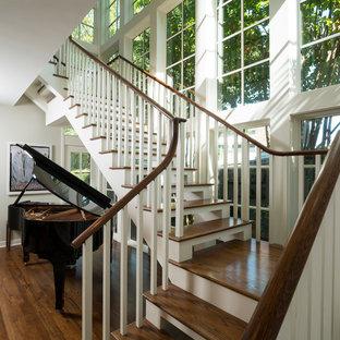 Imagen de escalera en L, de estilo americano, grande, sin contrahuella, con escalones de madera y barandilla de madera
