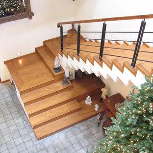 Ejemplo de escalera suspendida, tropical, grande, con escalones de madera, contrahuellas de madera y barandilla de metal