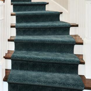 Ejemplo de escalera curva, clásica renovada, de tamaño medio, con escalones de madera y contrahuellas de madera pintada
