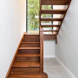 Ispirazione per una grande scala a rampa dritta moderna con pedata in legno, alzata in vetro e parapetto in vetro