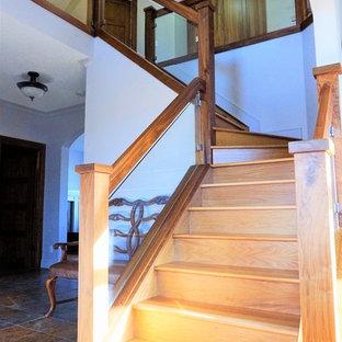 Foto de escalera en L, rústica, de tamaño medio, con escalones de madera, contrahuellas de madera y barandilla de vidrio