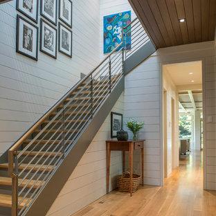 Imagen de escalera en L, clásica renovada, grande, con escalones de madera, contrahuellas de metal y barandilla de metal