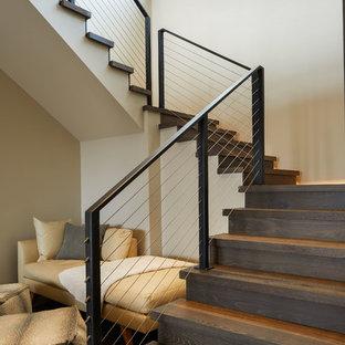 Modelo de escalera en L, rústica, de tamaño medio, con escalones de madera, contrahuellas de madera y barandilla de cable