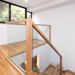 Ejemplo de escalera curva, bohemia, pequeña, con escalones de madera, contrahuellas de vidrio y barandilla de madera