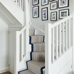 Foto på en maritim svängd trappa, med heltäckningsmatta, sättsteg med heltäckningsmatta och räcke i trä