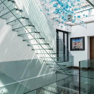Ejemplo de escalera suspendida, actual, grande, con escalones de vidrio y contrahuellas de vidrio