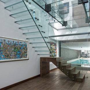 Foto de escalera suspendida, contemporánea, grande, con escalones de vidrio y contrahuellas de vidrio