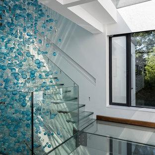 Exempel på en stor modern flytande trappa i glas, med sättsteg i glas