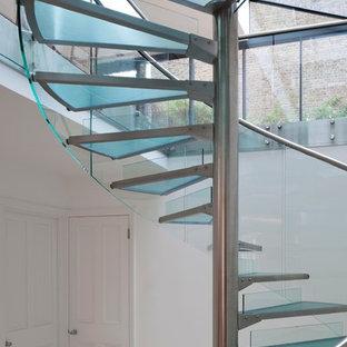 Ispirazione per una scala a chiocciola moderna con pedata in vetro e alzata in vetro
