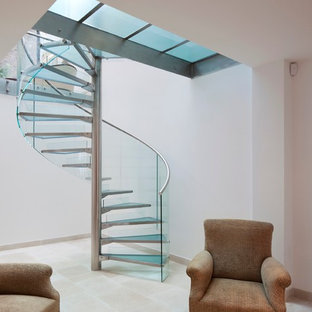 Staircase - modern glass spiral staircase idea in London with glass risers