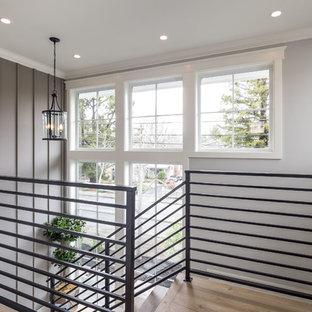 Diseño de escalera en U, de estilo de casa de campo, de tamaño medio, con escalones de madera, contrahuellas de madera y barandilla de metal