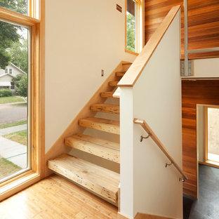 Imagen de escalera moderna, sin contrahuella, con barandilla de madera y escalones de madera
