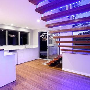 На фото: большая лестница на больцах в стиле модернизм с деревянными ступенями без подступенок с