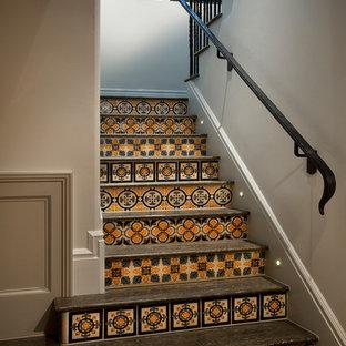 Foto de escalera en L, tradicional renovada, de tamaño medio, con barandilla de metal, escalones de madera y contrahuellas con baldosas y/o azulejos