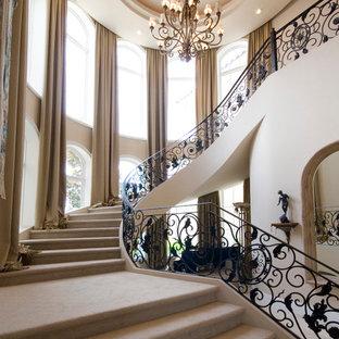 Foto de escalera curva, mediterránea, extra grande, con escalones enmoquetados, contrahuellas enmoquetadas y barandilla de metal
