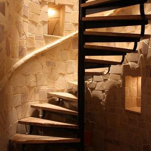 Esempio di una grande scala a chiocciola country con pedata in legno e nessuna alzata